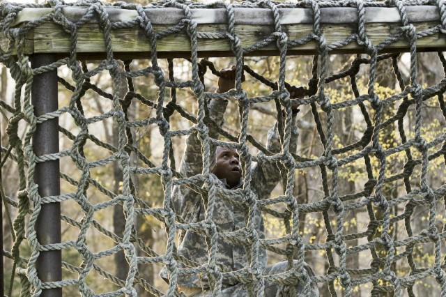 Staff Sgt. Myron Wade, an observer coach/trainer with 2-305th Field Artillery Battalion, 177tth Armor Brigade, climbs a cargo net at Beaudoin Obstacle Course at Fort Knox, Ky.,  April 10. The course was one event in First Army Division East's quarterly Best Warrior competition, hosted by 4th Cavalry Brigade. (U.S. Army photo by Sgt. 1st Class Gary J. Cooper, 4th Cavalry Brigade, Division East Public Affairs)