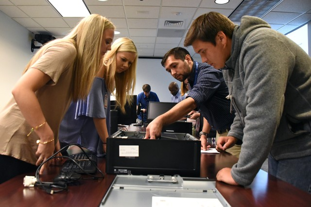 Andrew Chavez, network analyst, U.S. Army Space and Missile Defense Command/Army Forces Strategic Command, second from right, helps from left: Meredith McBride, 16; Maddie McBride, 14; and Carson Moon, 16, reassemble a computer in SMDC's Future Warfare Center's Simulation Center during Bring Your Daughters and Sons to Work Day April 27. Meredith and Maddie are the daughters of Marshall McBride, SMDC FWC engineer, and Moon is the cousin of Dana Henslee, SMDC's Internal Review Office.
