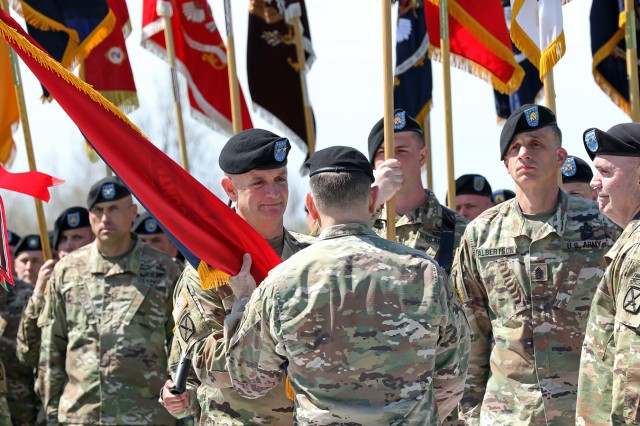 Gen. Robert B. Abrams, commanding general, U.S. Army Forces Command, passes the division colors to Maj. Gen. Walter E. Piatt, 10th Mountain Division (LI) and Fort Drum incoming commander, during a change of command ceremony Thursday on Fort Drum's Sexton Field, as Maj. Gen. Jeffrey L. Bannister, outgoing commander, looks on at right.