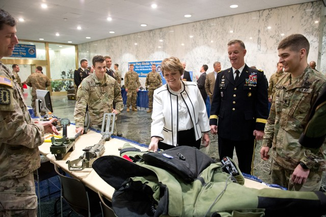 New York State Sen. Patty Ritchie and Maj. Gen. Walter E. Piatt, 10th Mountain Division (LI) and Fort Drum commander, stop by the display where explosive ordnance disposal Soldiers talk about their profession and equipment. A contingent of Fort Drum leaders and Soldiers traveled to Albany on Tuesday for 10th Mountain Division and Fort Drum Day.
