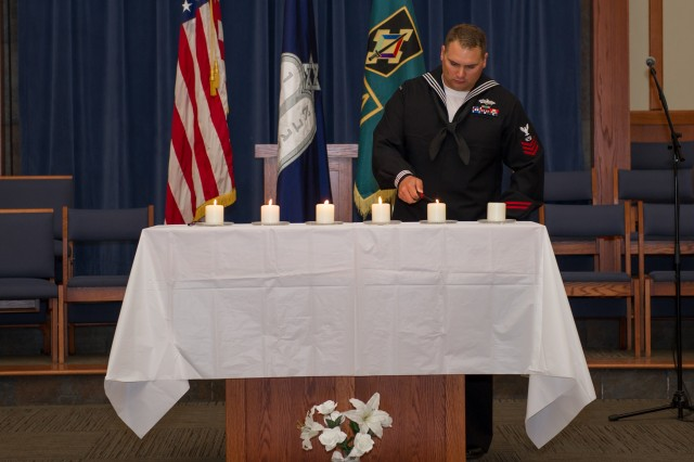 Petty Officer 1st Class Christopher Hartke lights the fifth candle honoring Holocaust victims at the Days of Remembrance Observance April 26 at the Main Post Chapel. Photo by Angi Betran/Visual Information Center