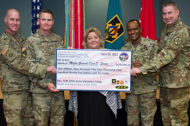 Rhonda Hutsell, Army Volunteer Corps coordinator, center, presents a ceremonial check for more than $1.9 million to Fort Leonard Wood leaders during the Installation Volunteer Awards Recognition Ceremony April 26 at Pershing Community Center. Photo by Angi Betran/Visual Information Center