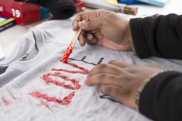 A t-shirt gets decorated at the Clothesline Project booth during Camp Zama's Cherry Blossom Festival April 1. All T-shirts created during the festival were later displayed along the route of the Sexual Harassment/Assault Response and Prevention Run April 21. (U.S. Army photo by Honey Nixon)