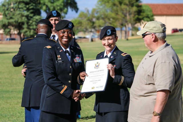 Sgt. 1st Class Derrick Oliver, Secretary General Staff noncommissioned officer in charge, Network Enterprise Technology Command (NETCOM), receives his certificate of retirement from Col. Wendy Rivers, commander, Information Systems Engineering Command, at the installation's quarterly retirement ceremony April 21 at Brown Parade Field, Fort Huachuca, Arizona.  (Photo Credit: Fort Huachuca Public Affairs Lara Poirrier)