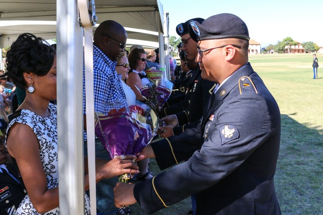 Flowers are presented to the spouses of the retiring military members in appreciation for their dedication and support at the installation's quarterly retirement ceremony April 21 at Brown Parade Field, Fort Huachuca, Arizona.  (Photo Credit: Fort Huachuca Public Affairs Lara Poirrier)