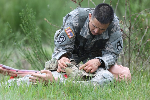 Sgt. 1st Class Fernando Terrazas, an observer coach/trainer assigned to 5th Armored Brigade, evaluates a casualty during the all-First Army Best Warrior Competition, at Joint Base Lewis-McChord, Wash., May 2-4. (Photo by Army Sgt. 1st Class Reshema Sherlock, 189th Combined Arms Training Brigade Public Affairs) (Photo Credit: U.S. Army)