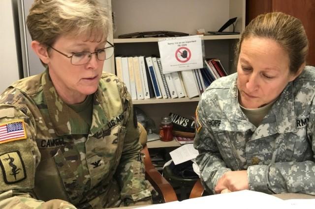Army Nurse, Col. Wendy Campbell and Maj. Susan Hopper discuss the senior nurse case managers' workload chart.