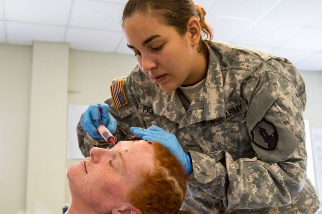Elsamari Figueroa, an ammunition specialist with the 266th Ordnance Company out of Aguadilla, Puerto Rico, prepares a fake head wound on a civilian role-player as part of the Guardian Response exercise April 29, 2017, at the Muscatatuck Urban Training Center, Ind. Nearly 4,100 Soldiers from across the country are participating in Guardian Response 17, a multi-component training exercise to validate U.S. Army units' ability to support the Defense Support of Civil Authorities (DSCA) in the event of a Chemical, Biological, Radiological, and Nuclear (CBRN) catastrophe.