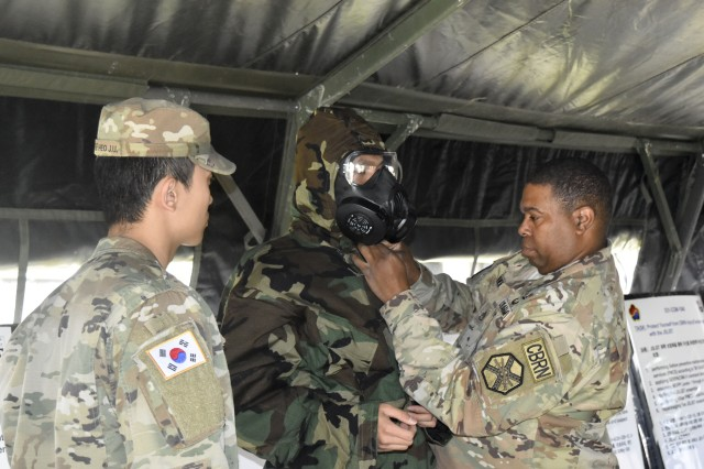Staff Sgt. Joseph Brown, HHC, USAG Daegu, demonstrates how to properly wear protective mask at Camp Henry on Apr. 24.