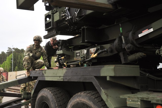Acting Secretary of the Army Robert Speers, right, climbs onto a Patriot Missile launcher from 10th Army Air and Missile Defense Command, to get an up-close view as missiles are loaded onto the vehicle, May 8, at Miesau Army Depot, Germany. Speers visited as part of a tour of Army operations in Europe.