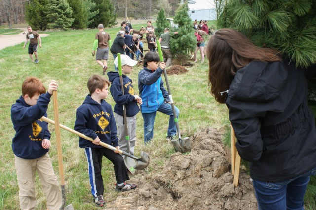 Scouts from Fort Drum Pack 26 take a break after digging a hole to plant a large Spruce tree at Zenda Farms Preserve April 29 in Clayton, New York, for Arbor Day. The Scouts volunteered to help plant trees as part of their community service project.