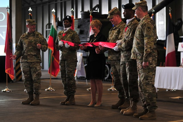 Dulmen City Mayor Lisa Stremlau and Maj. Gen. Duane A. Gamble, commanding general, 21st Theater Sustainment Command, cut the ribbon to officially open the Army Prepositioned Stock Site -- 2, at Dulmen Army Depot, Dulmen, Germany, May 10. The site will house a brigade's worth of vehicles and equipment as a part of NATO deterrence operations.