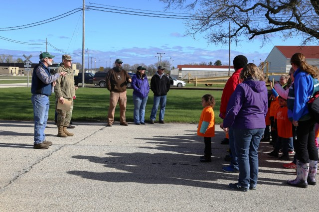 Forester James Kerkman (left) with the Forestry Office of the Directorate of Public Works Environmental Division Natural Resources Branch talks with adults and children from the Fort McCoy community during the installation observance of Arbor Day on April 28, 2017, at Fort McCoy, Wis. More than 30 people participated in the event that included a presentation of the 28th consecutive Tree City USA award for Fort McCoy as well as the planting of 320 trees along the cantonment area fence line. (U.S. Army Photo by Scott T. Sturkol, Public Affairs Office, Fort McCoy, Wis.)