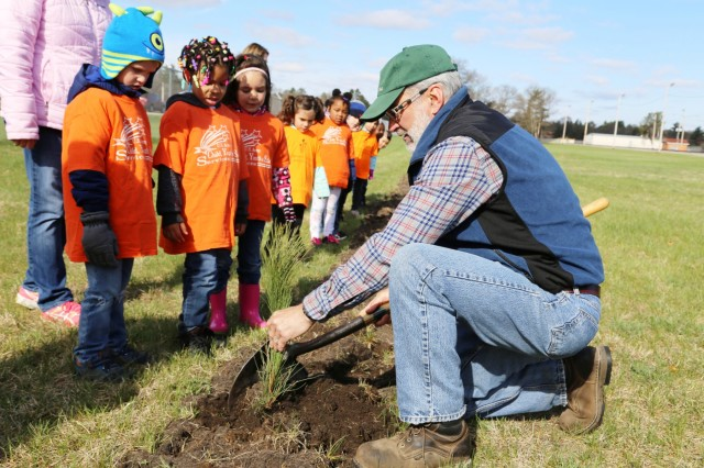 Forester James Kerkman (right) with the Forestry Office of the Directorate of Public Works Environmental Division Natural Resources Branch shows adults and children from the Fort McCoy community how to properly plant a tree during the installation observance of Arbor Day on April 28, 2017, at Fort McCoy, Wis. More than 30 people participated in the event that included a presentation of the 28th consecutive Tree City USA award for Fort McCoy as well as the planting of 320 trees along the cantonment area fence line. (U.S. Army Photo by Scott T. Sturkol, Public Affairs Office, Fort McCoy, Wis.)