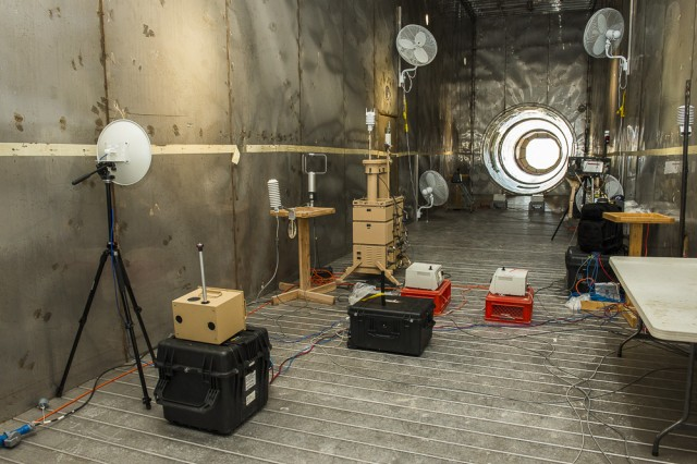 Interior detectors await the release of a simulated biological agent inside the Active Standoff Chamber at Dugway Proving Ground, Utah in 2015. The long chamber employs air downdrafts to contain the simulant, and allow lasers from exterior, distant detectors to penetrate and identify the agent. Glass or plastic walls might interfere with the lasers. Data collected by interior and exterior detectors is compared, to determine accuracy. Photo by Jim Robertson, Dugway Proving Ground Optics Branch