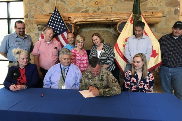 (SEATED SECOND FROM LEFT) RANDY MOORE, THE DIRECTOR OF FORT KNOX'S FAMILY AND MORALE, WELFARE AND RECREATION, (seated center) Garrison Commander Col. Steve Aiton and community members sign the community partnership memorandum of understanding Tuesday at Camp Carlson on Fort Knox.