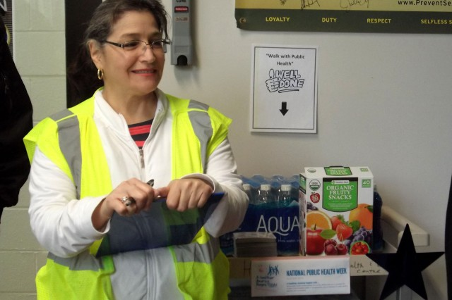 """LPN JANET MORALES PREPARES A HYDRATION CART, a sign-in sheet and gives a safety brief just before the """"Walk with Public Health"""" event. Part of her job of a public health nurse is to help set up programs such as this to help focus improving the health of individuals and the community."""