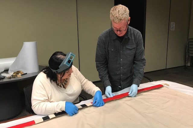 MUSEUM SPECIALIST AMBER HILLS AND EXHIBIT CONTRACTOR ROGER REIMAN PREPARE a large Nazi flag for display at the Patton Museum. General George Patton and the Western Task Force captured the flag in Casablanca, Morocco, in November 1942 during Operation Torch. It is believed to be the first German flag captured by the American Army in World War II. The museum began displaying the flag Tuesday.