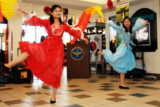 Shenglan Shi and Qiqi Liu, both of the Troy University Confucius Institute, perform a traditional fan dance during the Asian American/Pacific Islander Heritage Month kickoff ceremony at the post exchange May 5.