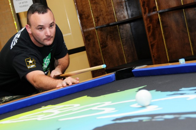 Spc. Joshua Moore, 1-212th Avn. Regt., enjoys a game of pool at the BOSS building. Moore was selected as one of five Soldiers to attend the 2017 Memorial Day ceremony at Arlington National Cemetery in Washington D.C.