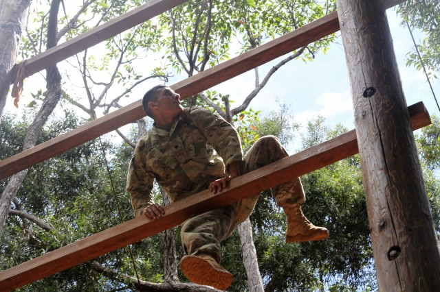 Specialist Avaristo R. Quintana with 8th Military Police Brigade, 8th Theater Sustainment Command, conquers the obstacle course for Day 2 of the Best Warrior Competition Army Physical Fitness Test May 9 at Schofield Barracks' East Range, Hawaii.