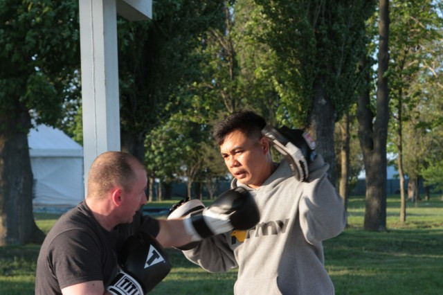 Sgt. 1st Class Joel Vallete, signal section chief of Headquarters Company, 1st Battalion, 8th Infantry Regiment, 3rd Armored Brigade Combat Team, 4th Infantry Division, conducts boxing mitt drills with one of his trainees on May 11, 2017 at Mihail Koglanicenau Air Base, Romania. Vallete, an All Army Boxing coach, uses boxing as a constructive way to spend free time with his fellow soldiers while on deployment in Romania, as well as sharing a passion of his with others. (Photo taken by Pvt. Nicholas Vidro, 7th Mobile Public Affairs Detachment)