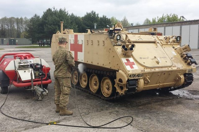 """A U.S. Army Soldiers with Company C, 64th Brigade Support Battalion, 3rd Armored Brigade Combat Team, 4th Infantry Division, washes an M113 Armored Medical Evacuation Vehicle in preparation for movement to Germany by rail at Skwierzyna, Poland, May 8, 2017. The """"Charlie Med"""" company has been busy on two fronts -- in Poland and Germany -- providing medical services and preparing for the brigade's participation in multinational exercises Combined Resolve VIII and Saber Guardian 17 as part of U.S. Army Europe's Atlantic Resolve mission. (U.S. Army photo by 3rd Armored Brigade Combat Team Public Affairs, 4th Infantry Division)"""