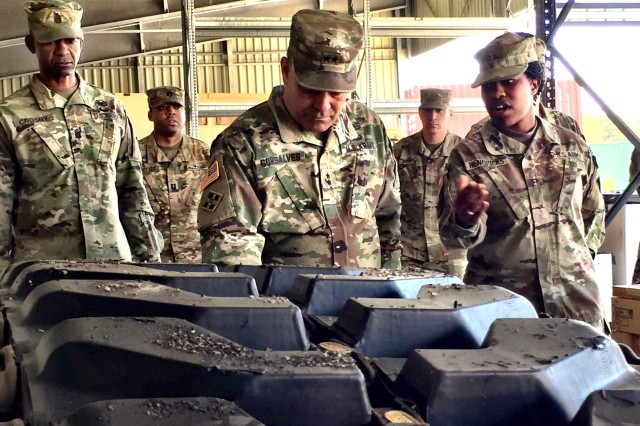 Chief Warrant Officer 2 Kyona Hendricks (right), supply support activity accountable officer, 64th Brigade Support Battalion, 3rd Armored Brigade Combat Team, 4th Infantry Division, explains how the SSA is processing a tank track for delivery as Maj. Gen. Ryan F. Gonsalves (center), commanding general, 4th Inf. Div. and Fort Carson, and Division Command Sgt. Maj. Michael A. Crosby (left) conduct a site visit of the brigade headquarters at Grafenwoehr Training Area, Germany, May 12, 2017. Gonsalves also delivered the U.S. Army Forces Command Supply Excellence Award SSA category second-place trophy to the SSA during the visit. The lessons learned during the competition have turned into streamlined delivery of parts across Europe as the SSA serves six other 3/4 ABCT battalions spread across eight countries as the brigade conducts Atlantic Resolve operations to deter aggression in eastern Europe.