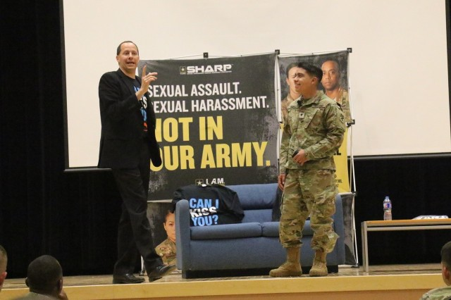 A soldier from the 11th Air Defense Artillery Brigade practices saying 'Can I kiss you?' in front of the audience during an interactive Sexual Harassment/Assault Response and Prevention training exercise at the Camp Carroll theater, May 15, 2017. The 19th Expeditionary Sustainment Command SHARP office hosted Mike Dortmitz's 'Can I Kiss You?' program in order to provide soldiers with a unique training focused on how to intervene to prevent sexual assault.