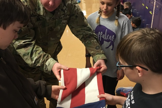 Sgt. 1st Class Ryan Neal, a research development test and evaluation non-commissioned officer in Operational Test Command's Maneuver Test Directorate, shows Florence Elementary School students how to tuck in edges and corners to get the best flag fold during flag etiquette training at Florence Elementary School, Florence Texas, on Jan. 20, 2017.