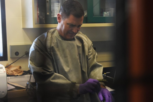 Maj. Gen. John Charlton, commander of Army Test and Evaluation Command, puts on latex gloves April 2017 in a lab at Dugway Proving Ground, Utah. He learned how personnel test defenses against chemical warfare agents for all services. Overall, the general commands nine Army testing facilities across the nation, each testing specific equipment used by all services. Photo by Al Vogel, Dugway Public Affairs