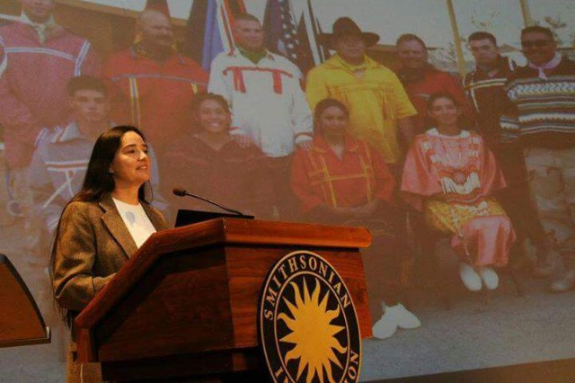 Retired Sgt. 1st Class Debra Kay Mooney speaks at the Smithsonian Institute's National Museum of the American Indian in Washington, D.C. Behind her is a photo of the pow-wow that she helped to organize in Iraq.