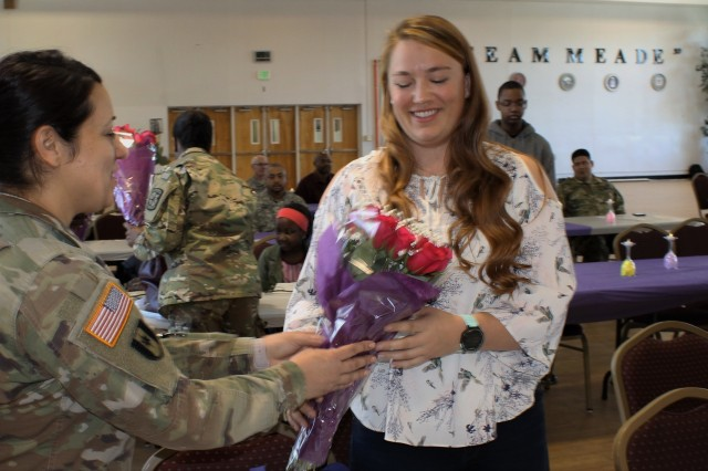 U.S. Army Sgt. Zahyra Yates, an Army Reserve Soldier assigned to the Army Reserve Cyber Operations Group (ARCOG), 335th Signal Command (Theater), presents flowers to a family member during a Welcome Home Warrior ceremony for Soldiers deployed from the ARCOG's North Capital Region Cyber Protection Center, April 2 at Fort Meade, Md. The NCRCPC Soldiers were deployed to Kuwait to conduct cyber training and missions in support of U.S. Army Central Command.