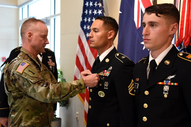 Col. Tim Lawson, deputy commander for support, U.S. Army Space and Missile Defense Command/Army Forces Strategic Command, presents Army Commendation Medals to Staff Sgt. Christian Budeshefsky, SMDC's 2017 Noncommissioned Officer Best Warrior, and Spc. Samuel Leznik, SMDC's 2017 Soldier Best Warrior, during a ceremony at the command's Peterson Air Force Base, Colorado, Operations headquarters, May 11.