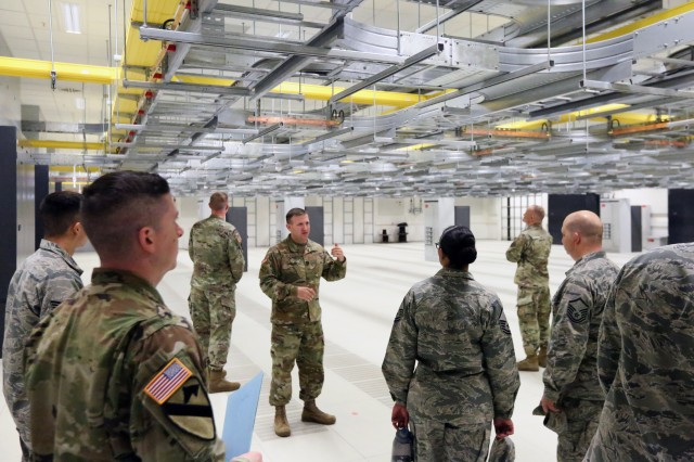 Capt. Matthew de la Guardia (center), commander of U.S. Army Signal Activity Kaiserslautern, leads a tour of the new USASA-K headquarters and operations building after a ribbon cutting ceremony to officially open the new facility May 15, 2017 in Landstuhl, Germany.