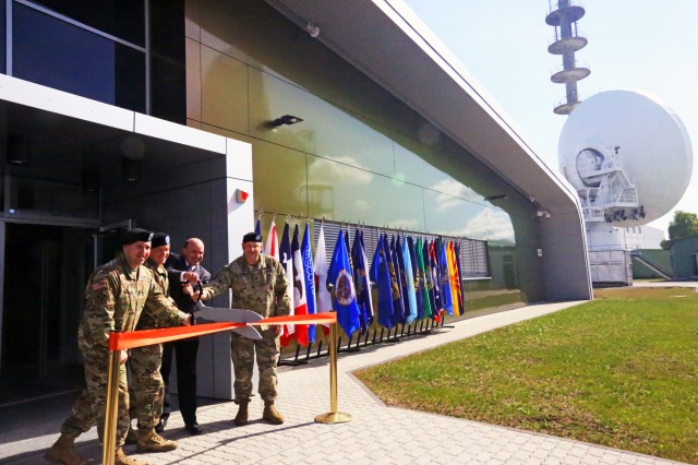 Capt. Matthew de la Guardia, commander of U.S. Army Signal Activity Kaiserslautern; Col. Jeff Worthington, commander of 2nd Theater Signal Brigade; John Adams, deputy district engineer of U.S. Army Corps of Engineers Europe District; and Lt. Col. Ernest Tornabell IV, commander of the 102nd Strategic Signal Battalion, cut a ribbon to officially open the new USASA-K headquarters and operations building at a ceremony May 15, 2017 in Landstuhl, Germany.