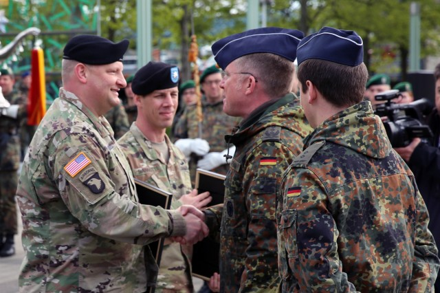 German Army Col. Ralf Hoffmann, Bundeswehr Communications and Information Systems Command deputy commander, presents a partnership certificate to U.S. Army Lt. Col. Ernest Tornabell IV, commander of the 102nd Strategic Signal Battalion, 2nd Theater Signal Brigade, at a partnership formalization ceremony April 25, 2017 in Bonn, Germany.