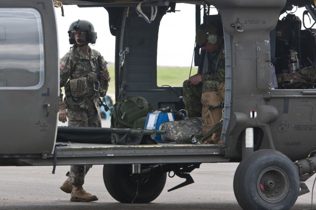 Sgt. Rebecca Himmel, a medic attached to the 1-169th Aviation Regiment, and Canadian Cpl. Jason Flegel, a forward aeromedevac specialist with the 2nd Field Ambulance, prepare to embark on a joint medevac training mission during Exercise Maple Resolve 17 at Camp Wainwright, Alberta, May 16, 2017. Exercise Maple Resolve is an annual collective training event designed for any  contingency operation. Approximately 4,000 Canadian and 1,000 U.S. troops are participating in Exercise Maple Resolve 17.