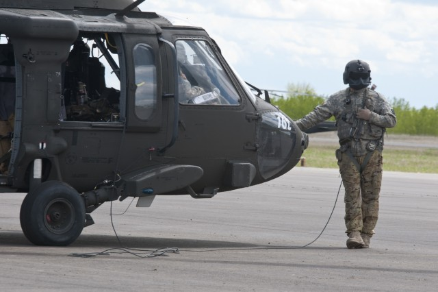 Sgt. Christopher Raynor, a crew chief with the 1-169th Aviation Regiment, prepares to embark on a joint medevac training mission during Exercise Maple Resolve 17 at Camp Wainwright, Alberta, May 16, 2017. Exercise Maple Resolve is an annual collective training event designed for any  contingency operation. Approximately 4,000 Canadian and 1,000 U.S. troops are participating in Exercise Maple Resolve 17.