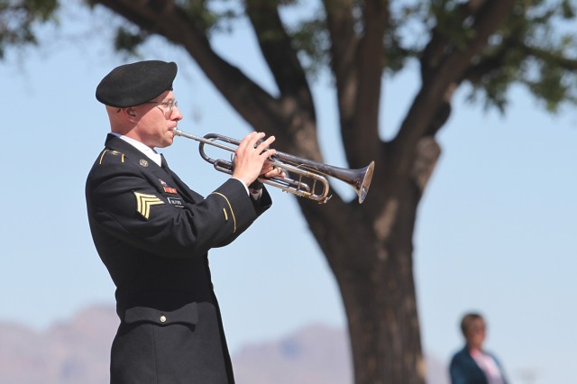 Sgt. William Milford, bugle player for the U.S. Army Military Intelligence Corps Band, plays Taps at the end of the ceremony May 17, in which the tile with the name and image of Sgt. 1st Class Allan E. Brown was added to the Signal Cove of Remembrance, inside Greely Hall, Fort Huachuca, Arizona.