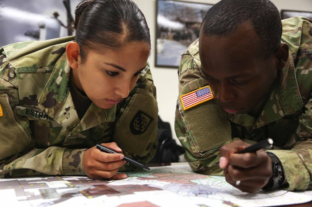 Pfc. Jessica Estrada (left) and Sgt. Eric Taylor, assigned to Headquarters Company, Network Enterprise Technology Command (NETCOM), plot their points during the land navigation training exercise for the NETCOM Best Warrior Competition at Fort Huachuca, Arizona, May 11, 2017. The land navigation training is designed to test the soldiers' abilities in teamwork and leadership as well as determining the grid coordinates on a military map.