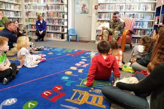 """WIESBADEN, Germany -- U.S. Army Garrison Wiesbaden Command Sgt. Maj. Larry Addington reads the book """"Courage"""" by Bernard Waber to children at the Wiesbaden Library May 20, 2017. After the story, Addington signed free copies of the book."""