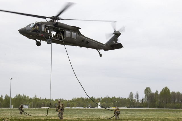 Soldiers from the Latvian Special Operations Forces (SOF) exit a UH-60 Black Hawk helicopter from C Company, 2-10 Assault Helicopter Battalion, 10th Combat Aviation Brigade, during a Fast Rope Insertion and Extration System (FRIES) training at Lielvarde, Latvia, on May 17. The brigade and members of the Latvian SOF worked together for an entire week to qualify members' skills for elite troop insertion techniques such as static-line parachutes, military freefall, and FRIES. (U.S. Army photo by Spc. Thomas Scaggs) 170517-A-TZ475-303