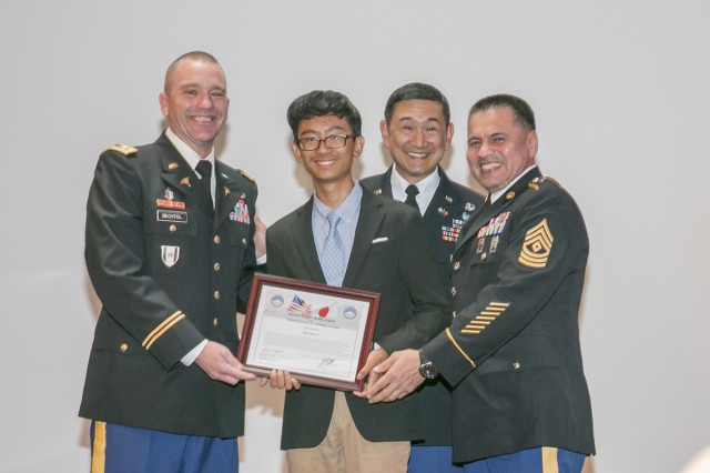 Dan Dalat, center, senior at Zama American High School, receives an award for introducing his father at the Asian American Pacific Islander Heritage Month Observance May 18, 2017 at Camp Zama Community Club. (U.S. Army photo by Honey Nixon)