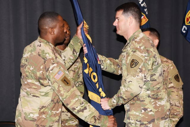 Mons, BELGIUM—Incoming Allied Forces North Battalion Commander, Lt. Col. Frank Jefferson receives the battalion colors from USANATO Brigade Commander, Col. Jason Riley, signifying Jefferson's assumption of command during a ceremony at SHAPE May 19. Jefferson assumed command from Lt. Col. Michael Minaudo who commanded the battalion for two years during which NATO organizations took on a renewed focus on readiness.