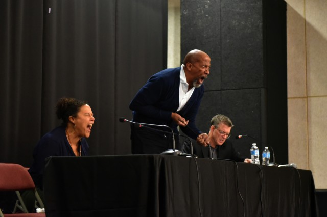 Actor Reg E. Cathey (middle), playing Ajax simulates the Greek warrior's suicide. Also shown are Linda Powell (left) playing Ajax's wife Tecmessa and Chris Henry Coffey (right) playing the chorus during Theater of War at the Camp Henry Theater on May 11. 2017.