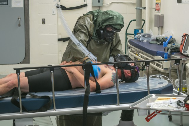 "Roger Graves, Chemical Defense Training Facility paramedic, checks cut-out ""victim,"" Staff Sgt. Kaleb Dombrain, for possible nerve agent contamination during an exercise at the CDTF Monday."