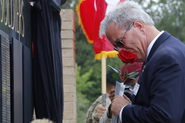 A grieving family member kisses a rose prior to placing it at the U.S. Army Special Operations Command memorial wall, below the name of his loved one during a memorial ceremony, May 25, at Fort Bragg. The ceremony was held in honor of the seven names added to the wall from the past year's casualties. (U.S. Army photo by Sgt. Kyle Fisch/Released)