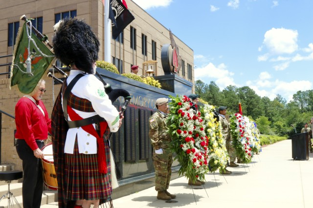 "Doug Elwell, the U.S. Army Special Operations Command regimental bagpiper, plays ""Amazing Grace"" at the USASOC memorial wall as tribute to the fallen warriors whose names were added to the wall during a memorial ceremony, May 25, at Fort Bragg. The ceremony was held in honor of the seven names added to the wall from the past year's casualties. (U.S. Army photo by Sgt. Kyle Fisch/Released)"
