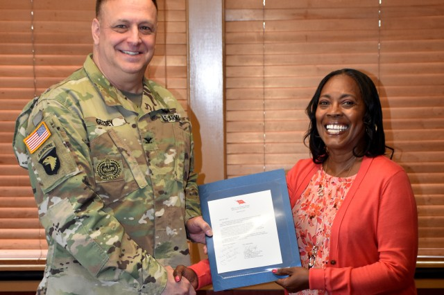 Col. William E. Geesey, commander U.S. Army Medical Materiel Development Activity, presents Teri Glass with a letter of recognition from Lt. Gen. Nadja Y. West, Army Surgeon General and commanding general U.S. Army Medical Command.
